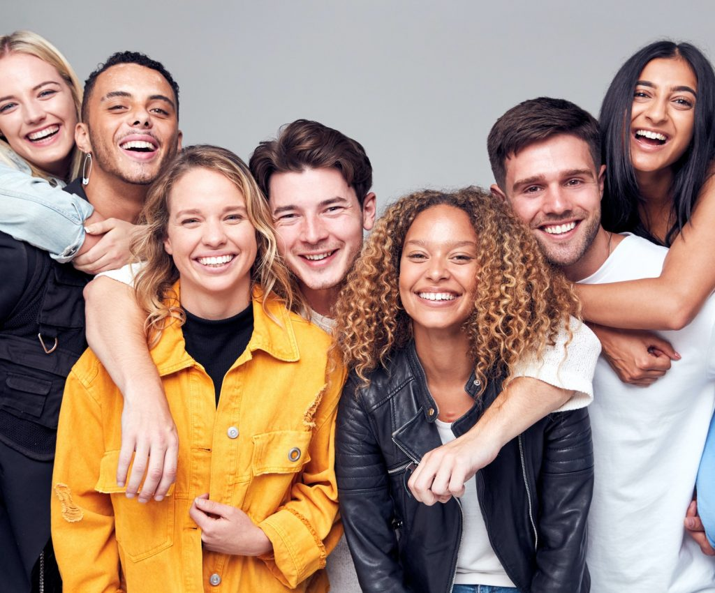 group-studio-shot-of-young-multi-cultural-friends-giving-each-other-piggybacks-and-smiling-at-camera